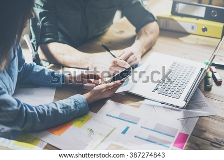 Marketing analysis team meeting concept. Young businessman crew working with new startup project in modern loft. Generic design notebook on wood table. Horizontal, film effect - stock photo