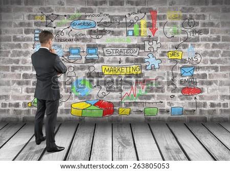 Marketing. Man drawing strategy on brick wall - stock photo
