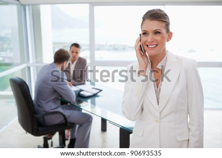 Marketing manager on the phone with her team sitting behind her - stock photo