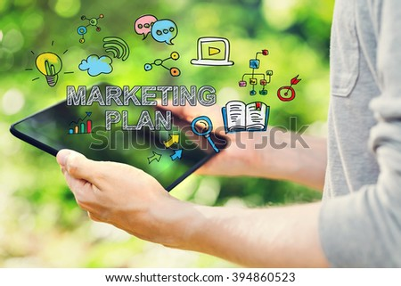 Marketing Plan concept with young man holding his tablet computer outside in the park - stock photo