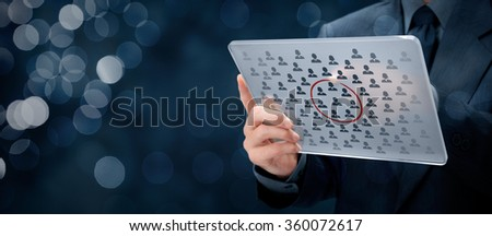 Marketing segmentation concept - businessman with futuristic glass tablet select segment (niche) of customers. Wide banner composition with bokeh in background.