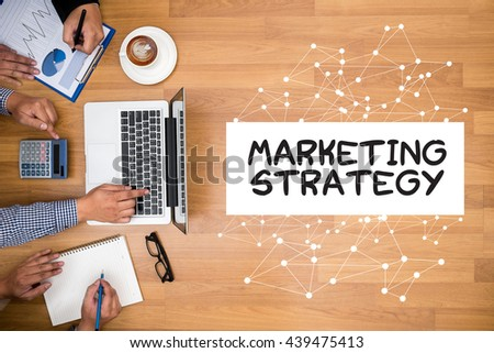 MARKETING STRATEGY Business team hands at work with financial reports and a laptop - stock photo