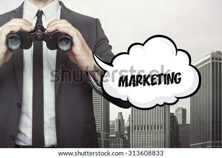 Marketing text on speech bubble with businessman holding binoculars on city background - stock photo