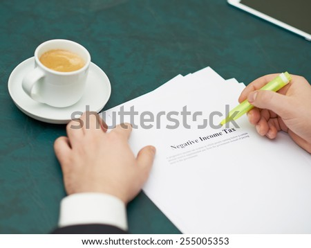 Marking words in a negative income tax definition, shallow depth of field composition - stock photo