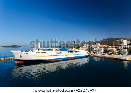Marmari port with anchored ship and white houses against a blue sky and blue waters in Evia, Greece - stock photo