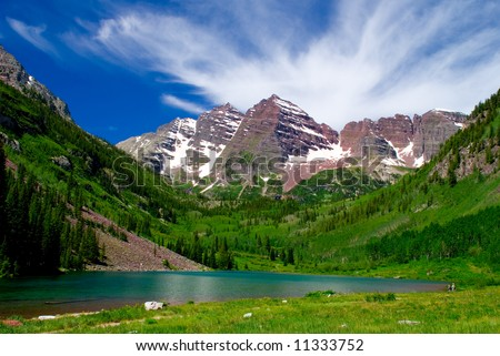 Maroon Bells Mountain Peaks in the summer with Marron Lake in foreground and two hikers on edge of lake - stock photo