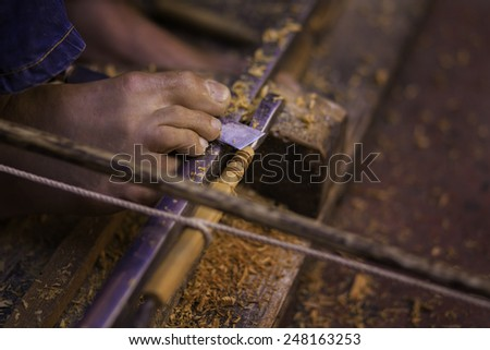 Marrakech/ Morocco - October 30th 2014: A moroccan carpenter using his feet to hold a chissel with a bow lathe. Marrakech, Morocco. - stock photo