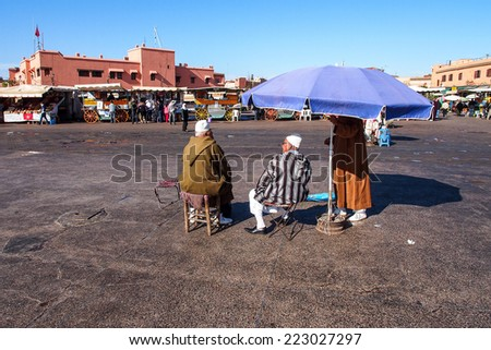 MARRAKESH - JANUARY 1: People in Jemaa el Fna Square at sunset, January 1, 2014 in a Marrakesh, Morocco. The square is part of the UNESCO World Heritage - stock photo