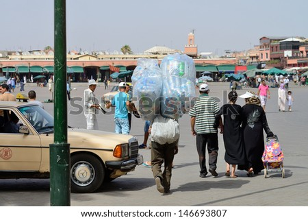 MARRAKESH - JULY 09: Unknown people walking at Djemaa el Fna square, July 09, 2013 in a Marrakesh, Morocco. The square is part of the UNESCO World Heritage. - stock photo