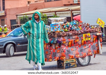 MARRAKESH, MOROCCO, APRIL 3, 2015: Jemaa el-Fnaa square -local seller and his stand with ceramic souvenirs - stock photo