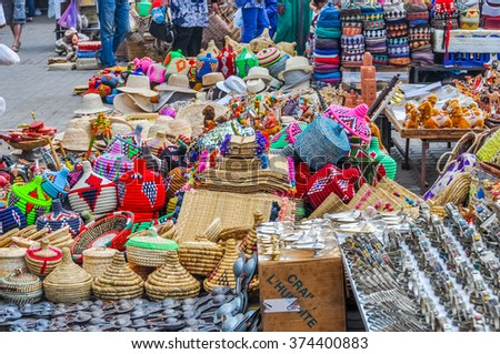 MARRAKESH, MOROCCO, APRIL 3, 2015:  Local sellers offer baskets and other souvenirs on street stands in souks - stock photo