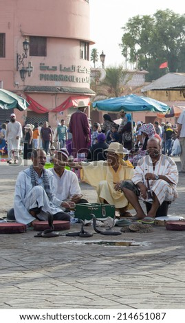 MARRAKESH, MOROCCO - AUGUST 24: Snake charmers in the Djemaa el Fna - market place in Marrakesh's medina quarter on 24 August 2014 in Marrakesh, Morocco. Djemaa el Fna is a UNESCO world heritage site. - stock photo