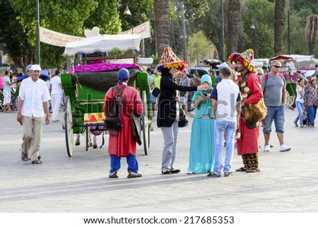 MARRAKESH, MOROCCO - AUGUST 24: Tourists visiting Djemaa el Fna - market place in Marrakesh's medina quarter on 24 August 2014 in Marrakesh, Morocco. Djemaa el Fna is a UNESCO world heritage site. - stock photo