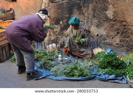 Marrakesh, Morocco - Jan, 02:  Men selling vegetables at a stand on January, 02, 2010. Marrakesh, Morocco. - stock photo