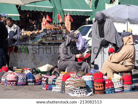 MARRAKESH, MOROCCO - January 2013: Unidentified women selling hand??made knitted  hats on the Jemaa el Fna Square in Marrakesh, Morocco. The square is part of the UNESCO World Heritage.  - stock photo