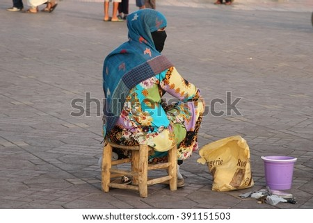 MARRAKESH, MOROCCO - JULY 11: A woman in full burka waiting for clients to paint henna on them in the Jemaa el Fna square in the old town of Marrakesh, Morocco on the 11th July, 2015. - stock photo