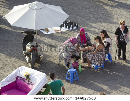 MARRAKESH, MOROCCO - JUNE 3: Unidentified people make henna painting on the Jemaa el Fna Square on June 3, 2013 in Marrakesh, Morocco. The square is part of the UNESCO World Heritage. - stock photo
