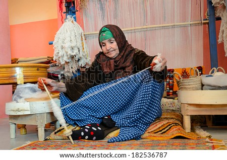 Marrakesh, Morocco - March 12, 2014: Senior woman spining a woolen string for berber moroccan carpets - stock photo