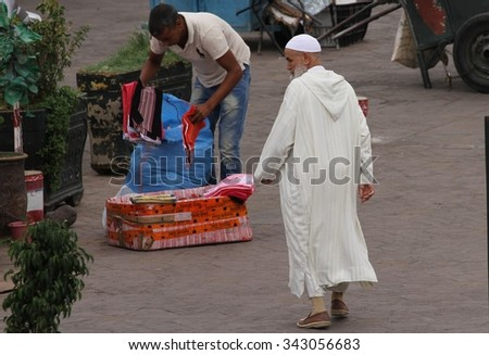 MARRAKESH, MOROCCO - OCTOBER 8: A local Muslim man in traditional dress in Jemaa el Fnaa Square, Marrakesh, Morocco on the 8th October, 2015. - stock photo