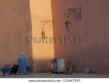 MARRAKESH, MOROCCO - OCTOBER 27: Unidentified woman walking at the sunset near the Koutoubia mosque in the city center on October 27, 2008 in Marrakesh, Morocco. The souk is part of UNESCO WH. - stock photo