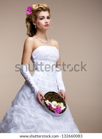 Marriage. Fashionable Bride Blonde in Bridal White Dress and Unusual Bouquet of Flowers - stock photo