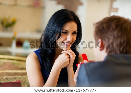 marriage proposal, man give ring to his girl, young happy couple romantic date at restaurant, celebrating valentine day - stock photo