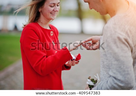 Marriage proposal. Man puts a finger engagement ring for his girlfriend - stock photo