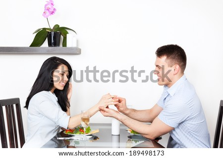 marriage proposal, man putting an engagement ring on woman finger, young happy couple dinner romantic date at restaurant, sitting at table celebrating - stock photo