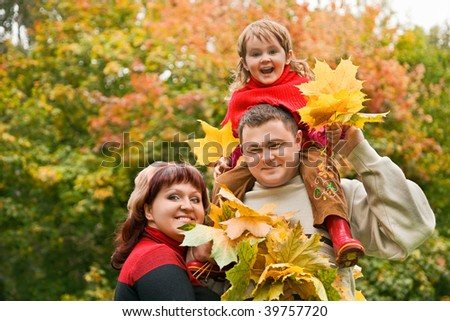 Married couple and little girl collect maple leafs In park in autumn - stock photo
