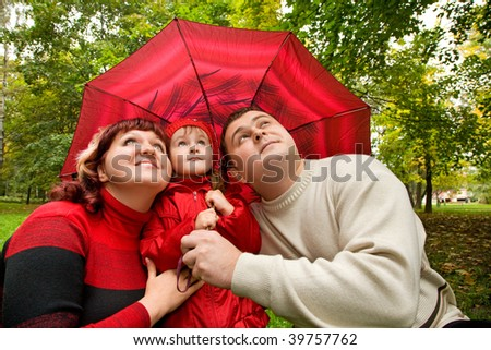 Married couple and  little girl on an umbrella in park - stock photo
