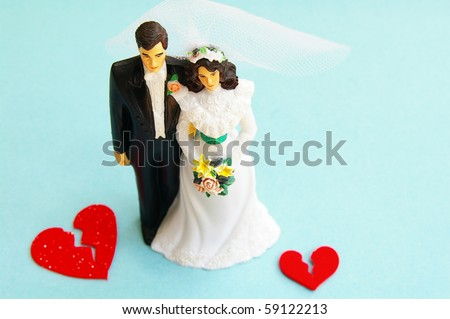 married couple figures and broken red hearts (divorce) - stock photo