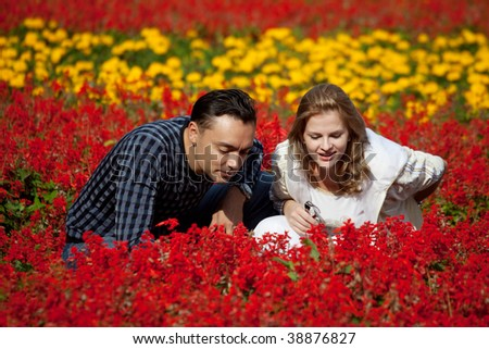 married couple looking at flowers in park - stock photo