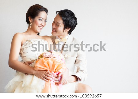 married couple sitting on chair.Groom hugging bride - stock photo