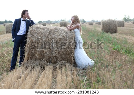 Married couple staring one another deeply in love, on a hay bale. - stock photo
