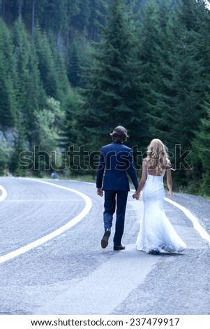 Married couple taking a walk on a highway near a wood. - stock photo