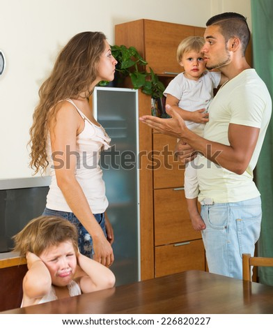 Married couple with two little children having conflict at home  - stock photo