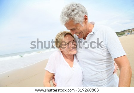 Married senior couple having fun walking in the beach - stock photo