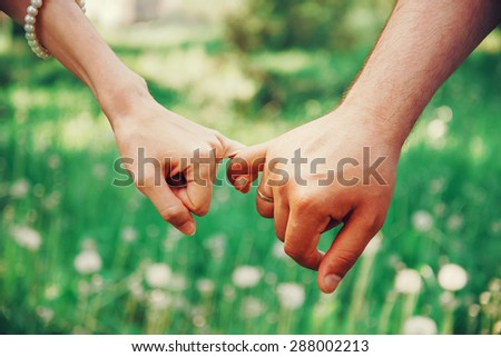 Married young loving couple holding hands each other in summer park, view of hands - stock photo