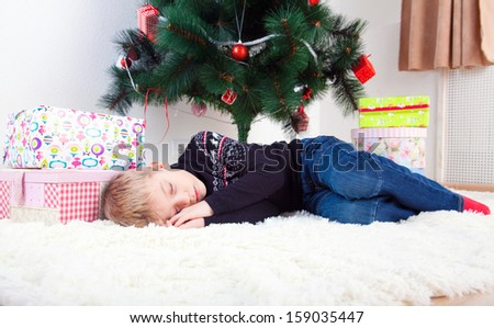 marry cristmas, little boy sleeping on the flor under the cristmas tree - stock photo