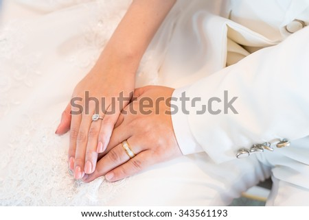 Marry me, Moment of LOVE, hands of a wedding heterosexual couple. Groom put a ring on finger of his lovely wife. - Selective focus. - stock photo