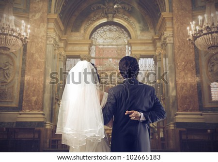 Marrying couple in a church with groom crossing his fingers behind his back - stock photo