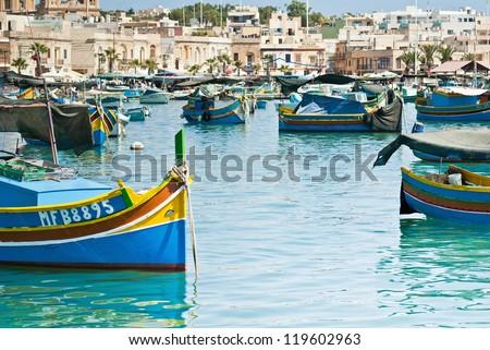 marsaxlokk malta old fishing village with ancient architecture and luzzu classic fishing boats in harbor mediterranean sea - stock photo