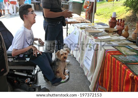 MARSEILLE, FRANCE - AUGUST 26: Photo of a young man in a wheelchair with his pet. Marseille Festival Association on August 26, 2012 in Park Borelli, Marseille, France - stock photo