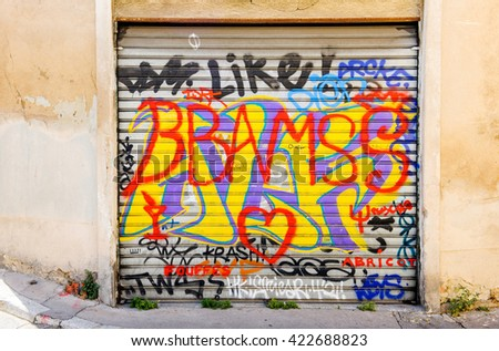 MARSEILLE, FRANCE - JUL 18, 2014: Old graffiti text on a garage door in the center of Aix-en-provence - stock photo