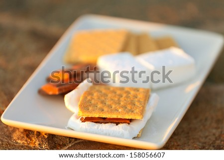 marshmallow, chocolate and graham crackers ready for smores making at the plate - stock photo