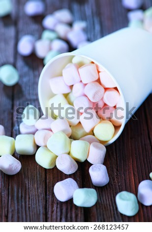 marshmallow in paper cup and on a table - stock photo