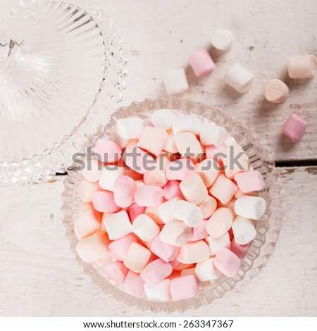 Marshmallows are small, colored in a glass vase. - stock photo