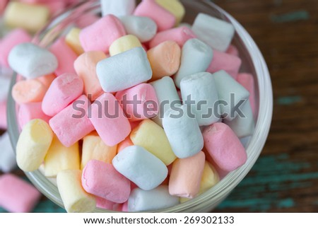 marshmallows in a bowl, wooden background. - stock photo