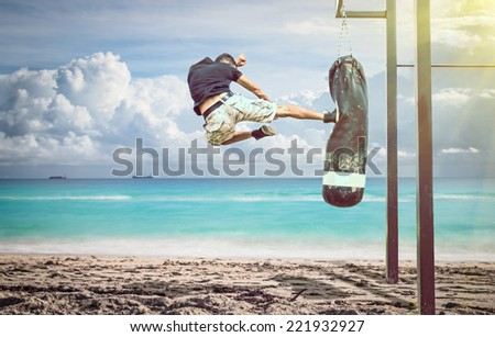 martial artist in action. performing a flying kick on a boxing bag on the beach. idyllic atmosphere - stock photo