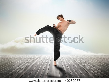 Martial arts fighter over wooden boards leading out to the horizon - stock photo